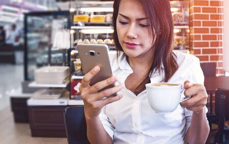 jeune femme buvant un café et utilisant une smartphone